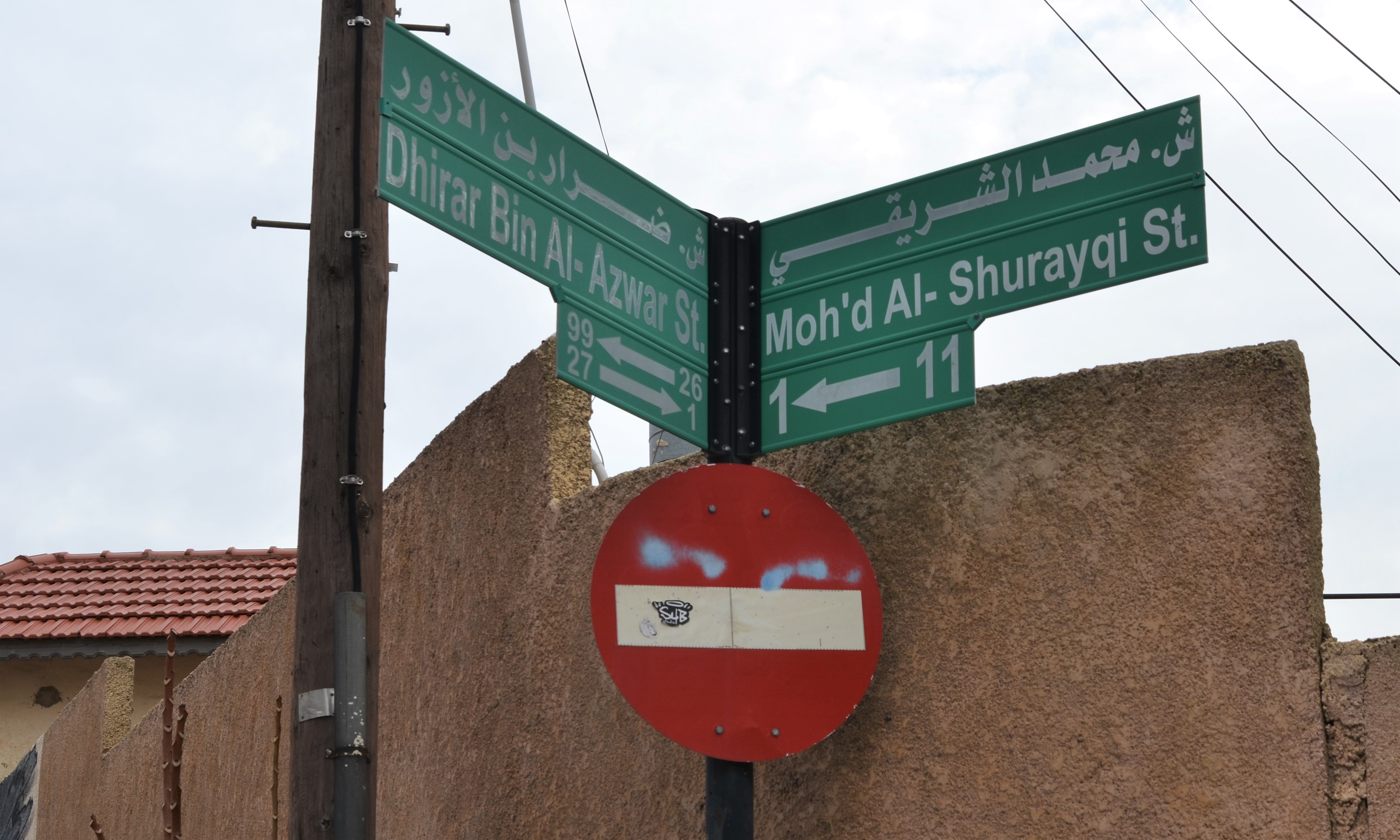 2 green street signs at an intersection in Amman Jordan along with a red and white do not enter sign