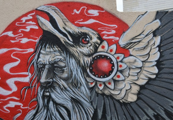 close up of head of bird in mural by Suhaib Attar in grey tones on red background