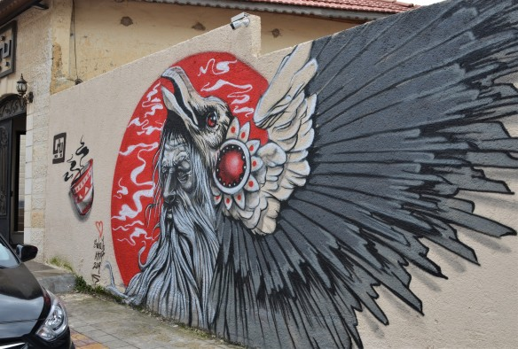 mural by Suhaib Attar of a bird with grey and black wing feathers, on red circle background