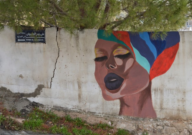 a woman in a colourful striped turban, singing with her eyes closed, mural pn a concrete wall, with green tree behind