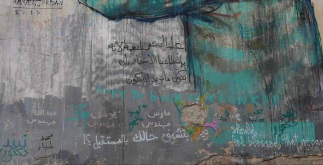 details of bottom portion of mural by Herakut, showing Arabic writing that others have added plus the words should feel blessed