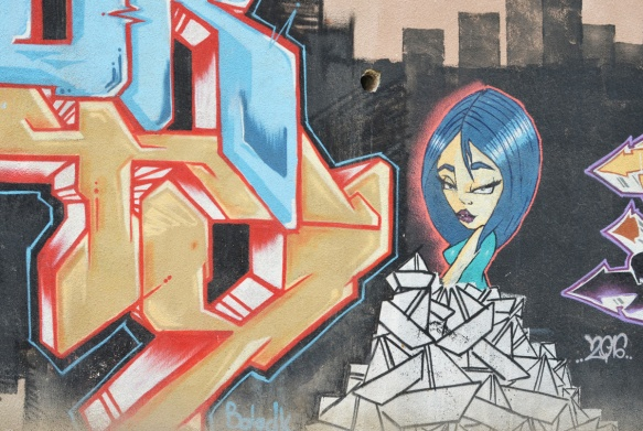 street art of a blue hair woman sitting on white paper boats