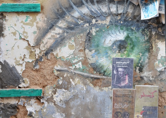 old and peeling street art painting of a green eye with lashes and eyelid on a wall with some books