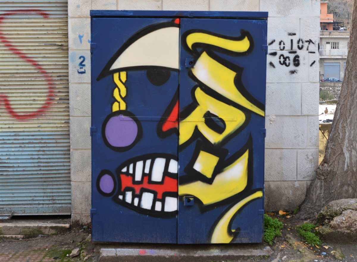metal box on street painted, dark blue background, left half is half a face while right side is Arabic letters in yellow