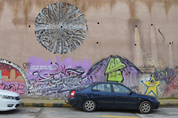 street art on a wall including a large grey circle made of Arabic calligraphy, a purple mass partially hidden by a car, and a yellow star with an eye
