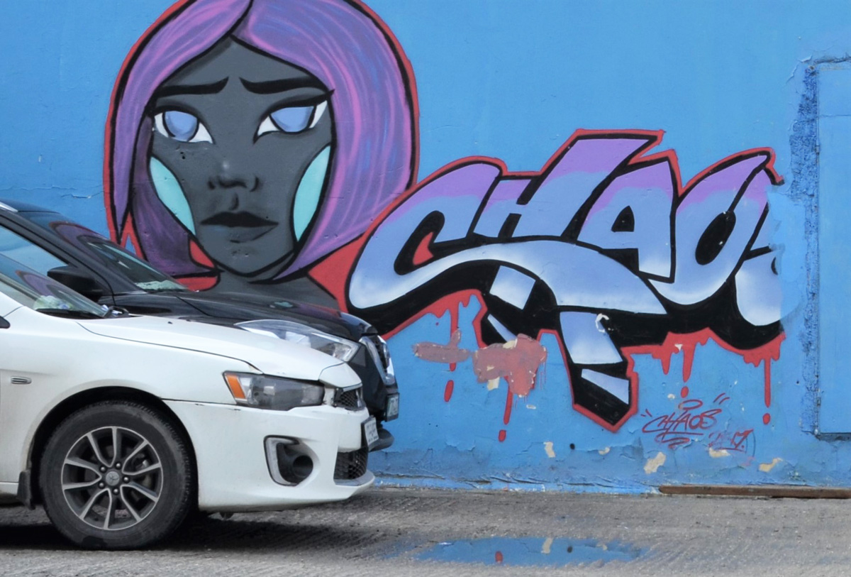 white car and black car parked in front of mural with a woman's face, purple hair, and text that says chaos