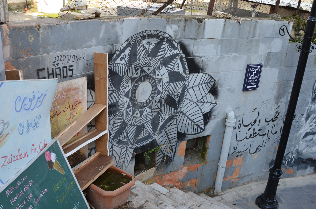 at a bend in an outdoor set of stairs, art cafe signs, street art on the wall, Jadal stairs, Amman