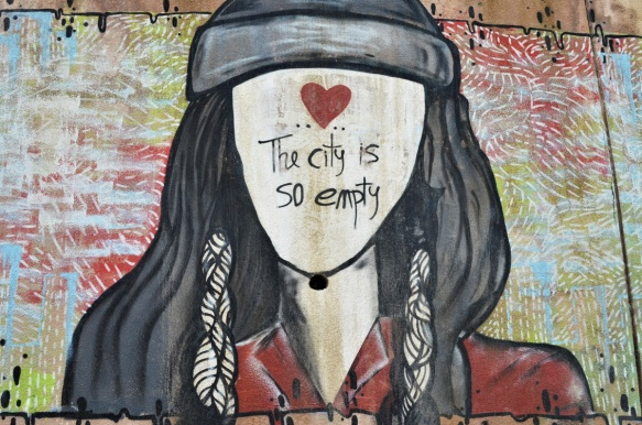 street art painting of a young woman with long black hair with a head band tied around her head, black face, no facial features, instead a red heart on her forehead and the words The city is so empty