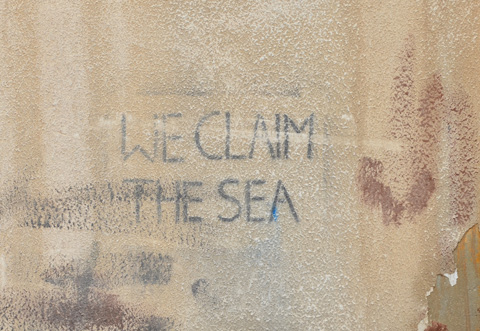 stencil on a wall, black letters that say we claim the sea