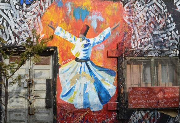 between two shuttered windows, a street art painting surrounded by white Arabic calligraphy on red, in the middle is the back of a dancer with red hat and long white robe tied at the waist, long skirt that twirls outward as dancer moves