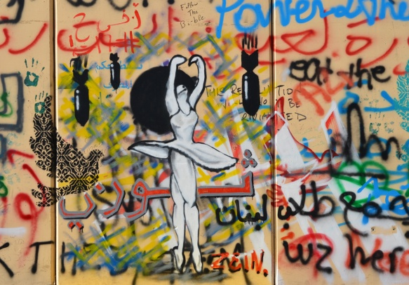white ballet dancer with skirt twirling as she spins, black bombs dropping around her. graffiti on a wall
