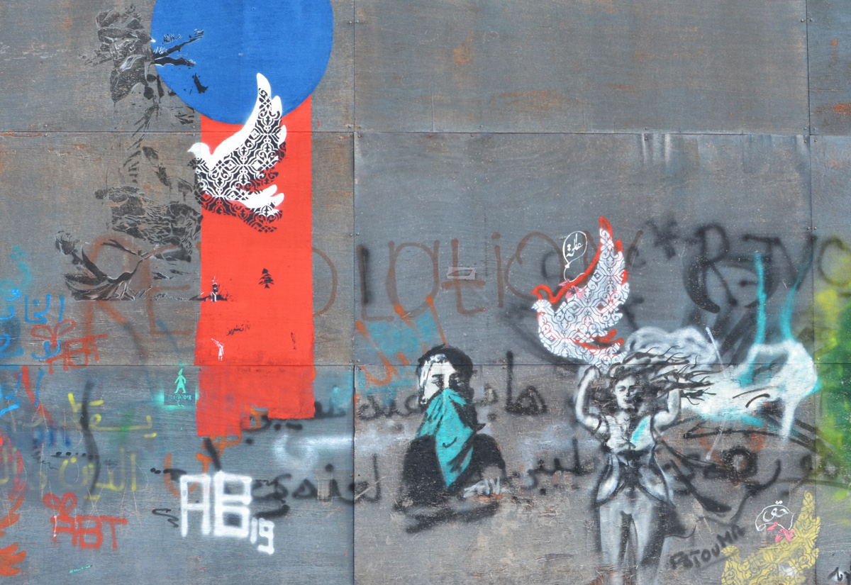 blue circle, red vertical stripe, black stencil of doves and other things in black along with a woman with a teal coloured bandana over the lower part of her face, a woman with long hair trying to hold onto a dove, all stencils