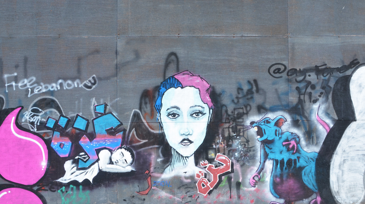 a woman's face with hair half blue and half pink, a large blue mouse that is screaming