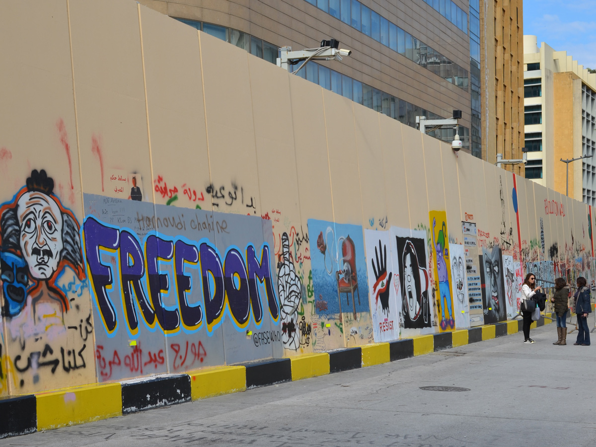 looking along a wall full of protest street art including a large word freedom