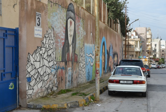 blue gate on the left, cars parked in front of, wall with street art, houses and other buildings in the background