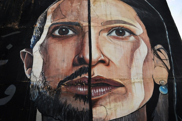 mural by herakut in Amman, very large face that is divided vertically down the middle, male on one side, female on the other,close up of eyes, nose and mouth