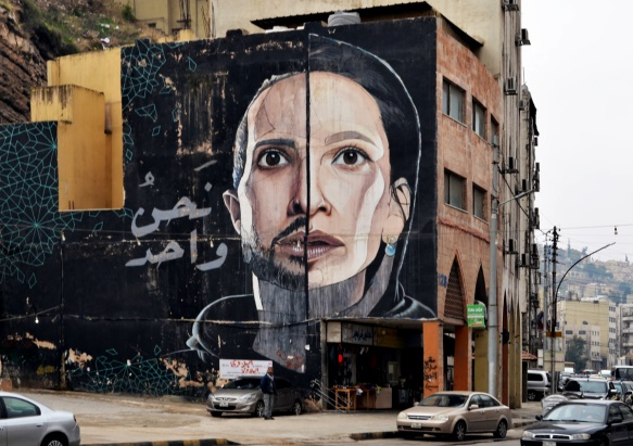 mural by herakut in Amman, very large face that is divided vertically down the middle, male on one side, female on the other, 4 storeys high, black background, man with beard and small moustache