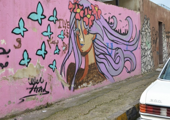 mural on pink background of a young woman with long purple hair, flower crown on her head, and blue butterflies flying nearby, head and shoulders
