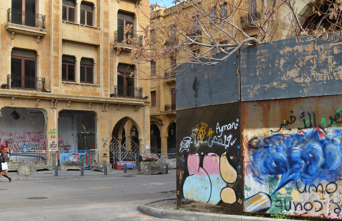 on a city street, low rise goldish brown stone buildings with graffiti and street art around the bottom layer