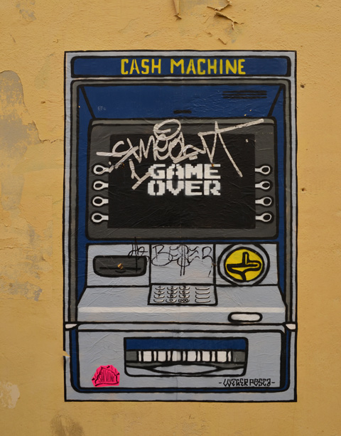 paste up graffiti on a wall in Rome, a picture of a cash machine as video game, monitor says game over