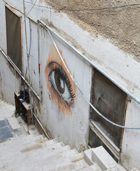 realistic painting of an eye on a wall between two windows on a set of stairs
