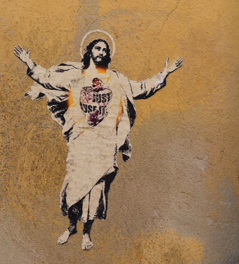 paper paste up of Jesus, white robes, halo, and arms reaching up