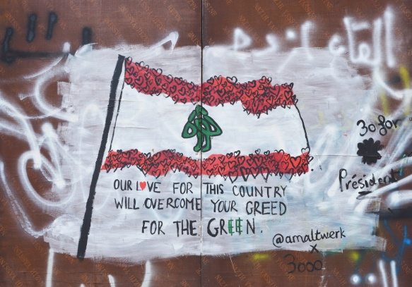 street art of a Lebanese flag with the red stripes made of hearts, also the words Our Love for the country will overcome your green for the green