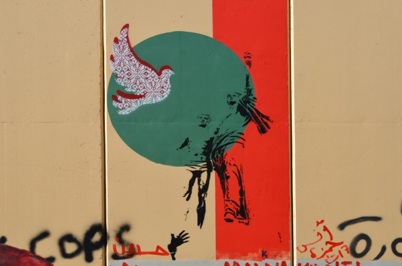 black stencil of two people looking into the distance, on top of a green circle along with a red and white dove
