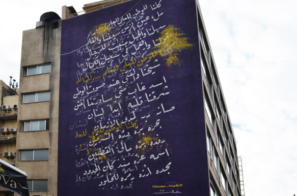 large mural on the side of a building in Hamras Beirut, purple background with white Arabic writing on it