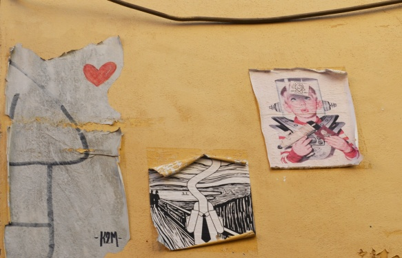3 paper paste ups on a yellow concrete wall, all three slightly faded and peeling at the edges, one is a K2M charaacter with a red heart, another is a black and white drawing similar to Edvard Munsch's Scream painting, and the last is a drawing of a young boy with ray gun and old fashioned idea of a space uniform
