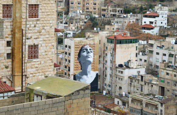large mural of a woman in grey tones, looking upwards with her eyes closed.  It covers the whole of one side of a multi storey building, Arabic writing around her