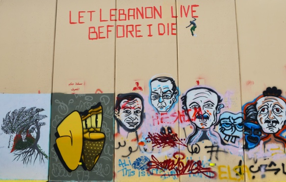 light brown temporary wall outside, made of panels, now home to a revolution wall of art and graffiti, white faces, a poster by sumerziady and the words let Lebanon live before I die