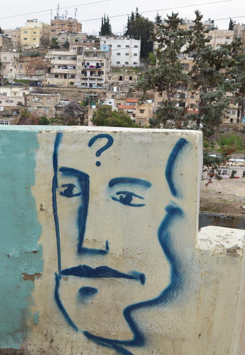 a blue line drawing of a man's face with a question mark on his forehead, painted on a short wall, view of Amman in the background