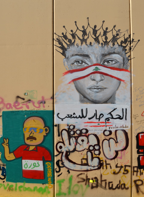 a head with stick figure people with arms upward as hair, and a strip of cloth in form of Lebanese flag across bridge of nose and cheeks, by Roula Abdo alongside a man in a red and white shirt on a green background, both graffiti on a wall