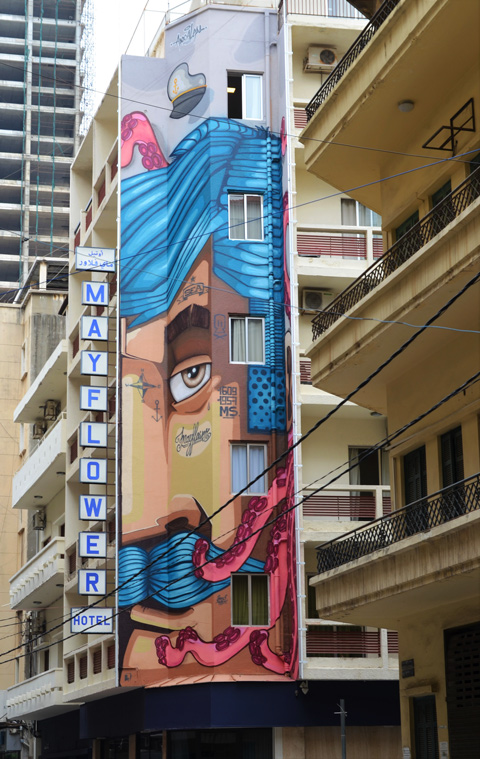 tall narrow mural of part of a man's face, with blue hair and blue mustache, by apocaleps