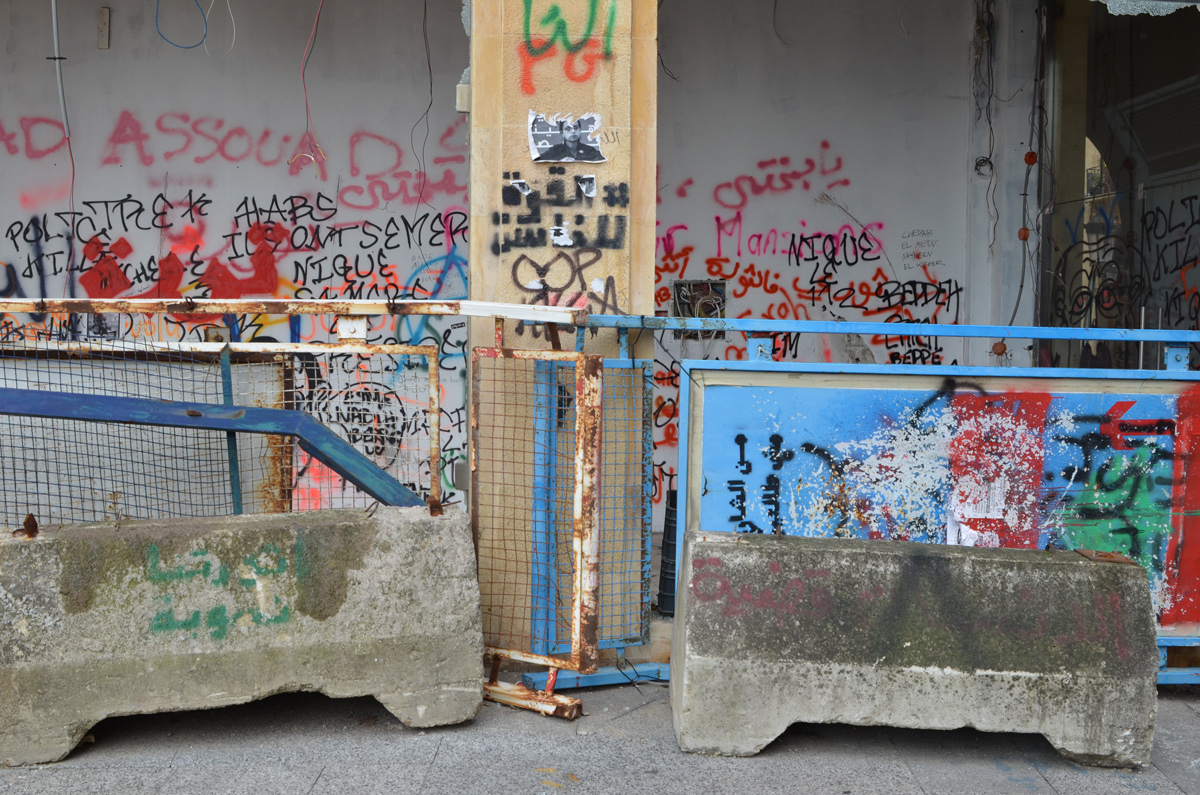 metal and concrete barricades beside a wall covered with tags and graffiti