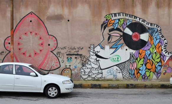 two white cars parked in front of a wall of Terra Sancta college with two murals on it, one by Suha Sultan with a woman with a Metallica Load vinyl record on the side of her head, and the other a pink shape