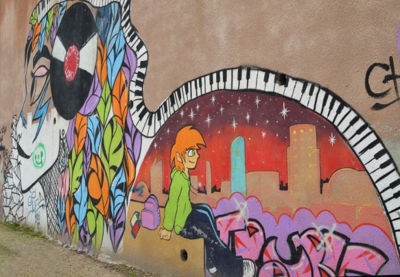 mural by Suha Sultan of a woman with a vinyl record on the side of her head, piano keys covering the top of the mural, a young boy sitting beside a cityscape behind the woman,