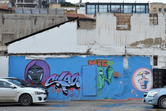cars parked in front of a blue mural on parking lot wall, a woman's face with text chaso, mig the robot, and a figure in pink