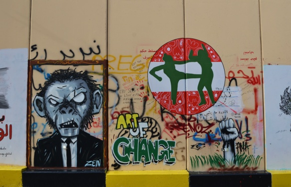 graffiti, a man with a monkey face, a red and white do not enter sign with two green figures fighting,