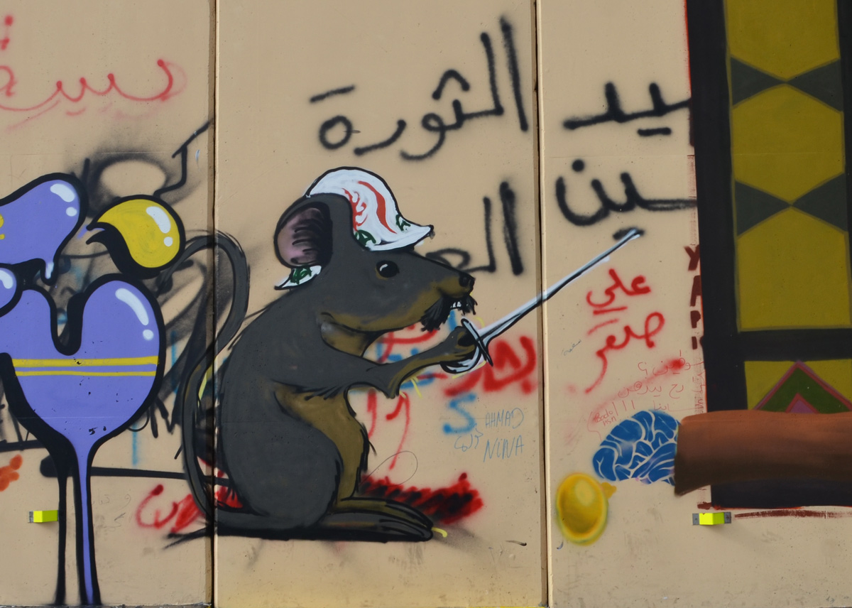 a grey mouse in a hard hat holding a sword, graffiti on a wall