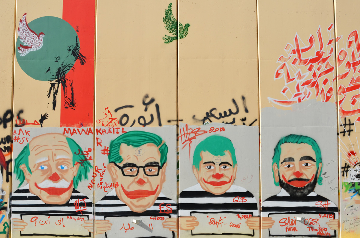graffiti on a Beirut wall, caricature mug shos of 4 Lebanese men, green hair and clown mouths, wearing black and white striped tops