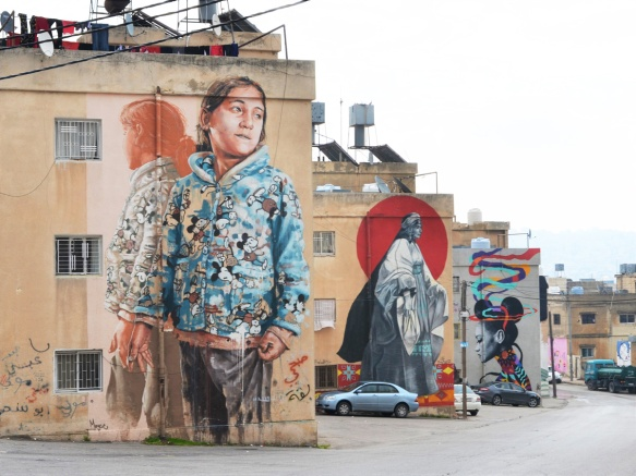 three large murals in a row, in the foreground is one of a girl by Finton Magee, the next is an old woman with a red circle in the background and the third is a colourful woman with ribbons by Dina Saadi