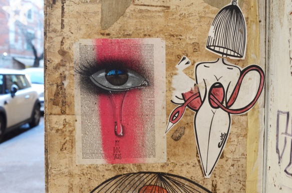 eye and red streak painted on a page of a book, now is graffiti, beside a pasteup of a woman with a birdcage for a head