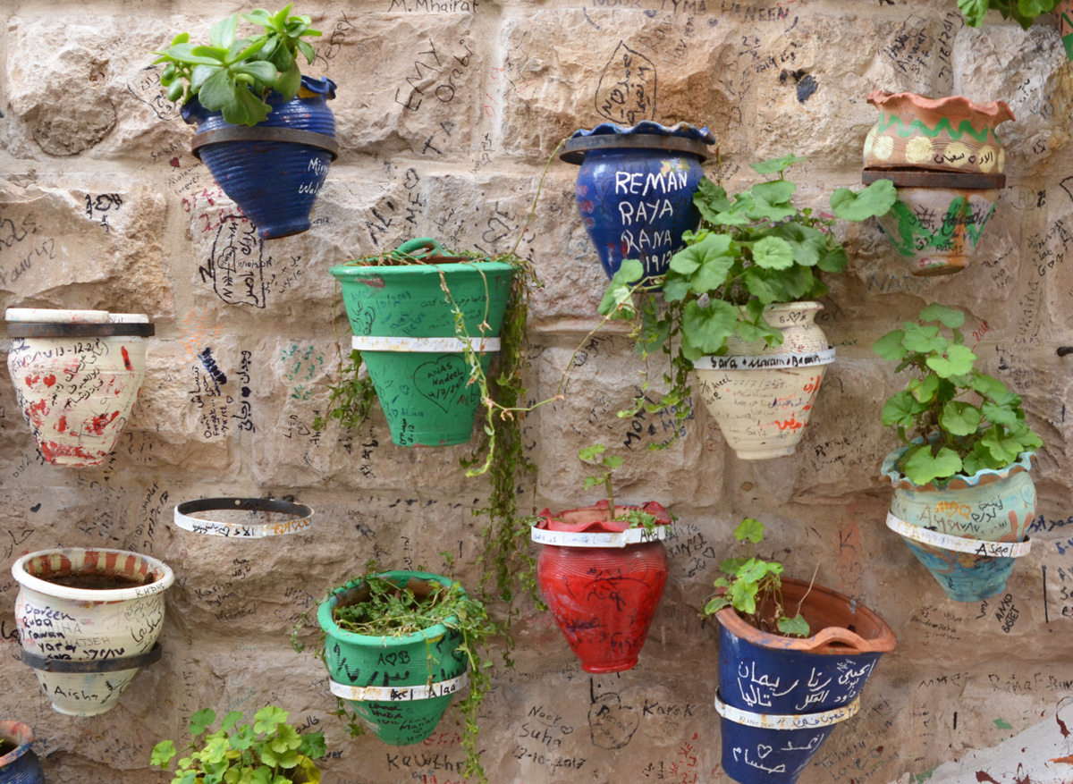 colourful flower pots attached to a wall with plants in them