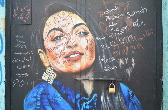 painting of a woman in a blue top on a black wall, that people have written their names on