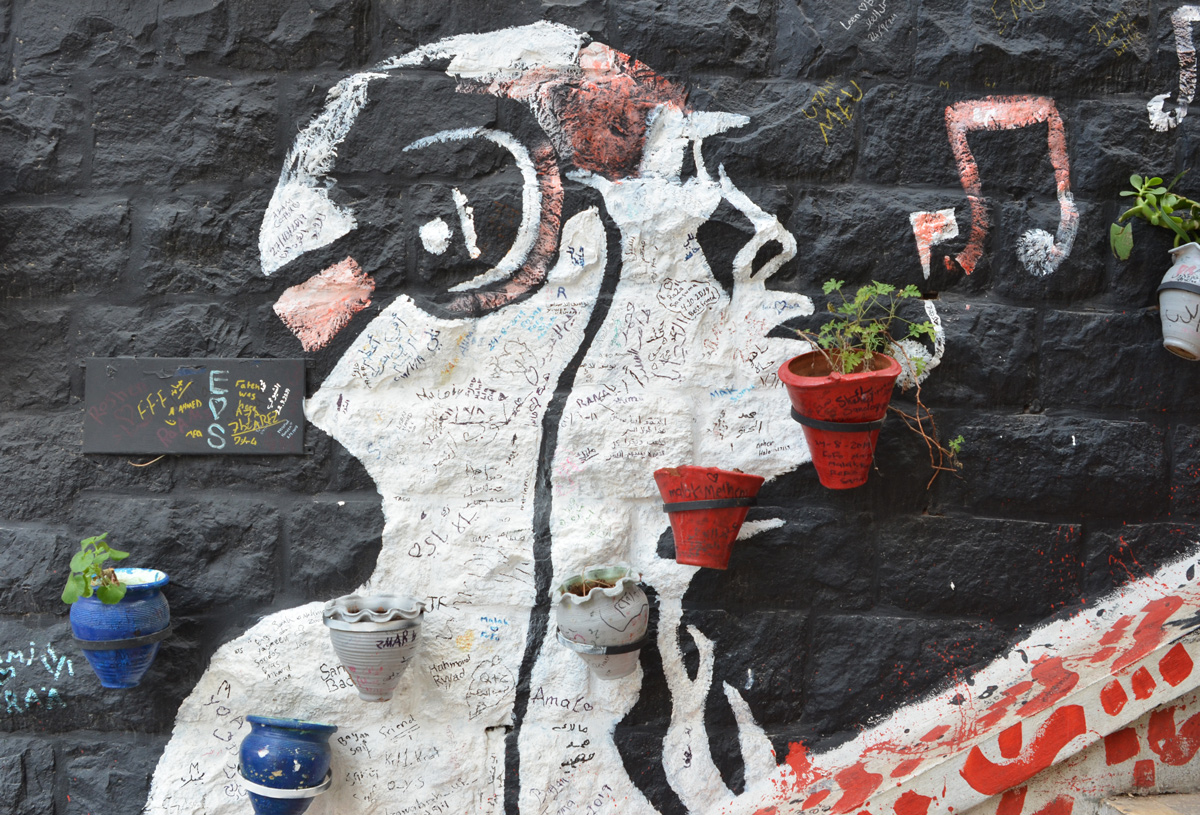 on a black wall, a profile silhouette in white of a man with headphones on, plants in terra cotta planters line the stairs that run beside the wall