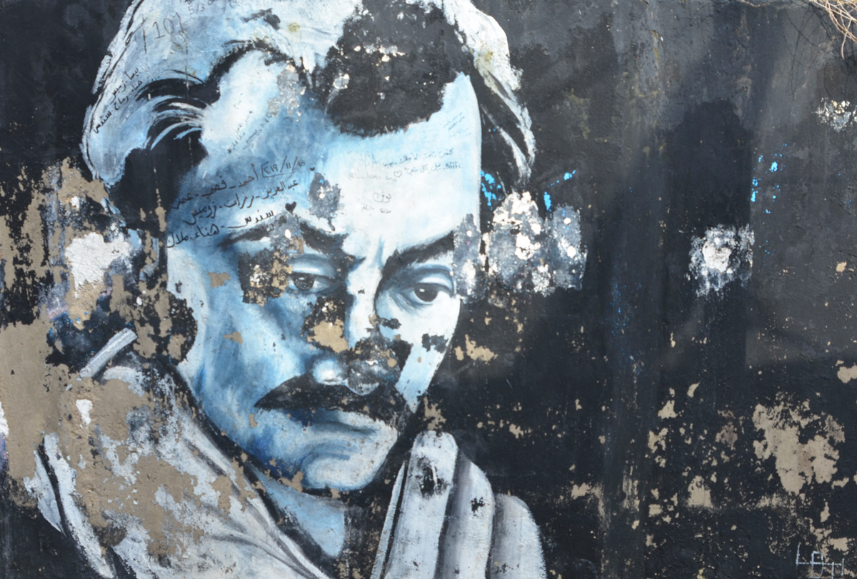 black and white street art painting of Omar Shariff on a black background, some of the paint has begun to peel off