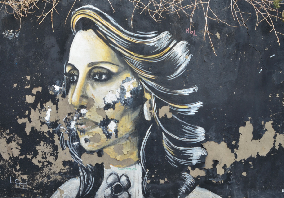 black and white street art painting of a woman on a black background, some of the paint has begun to peel off