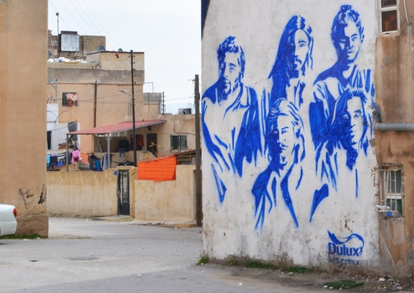 white background, blue paint, mural of a music group with 5 members, part of local vocals